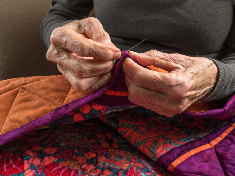 A Senior Woman Expertly Stitches the Binding Onto Her Quilt