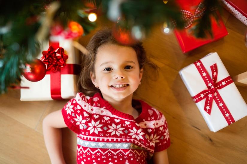 Little girl lying under Christmas tree among presents,